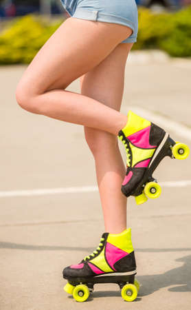 roller blade: Close-up of female legs in denim shorts riding roller skates.