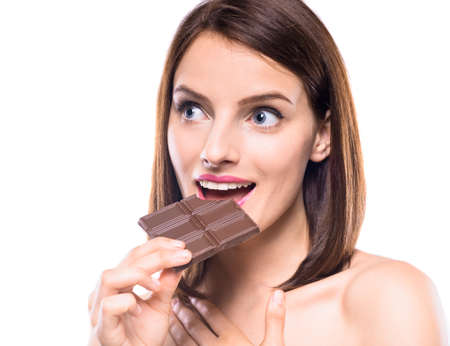 flirty: Flirty beautiful woman eating bar of chocolate and looking away. Studio shot. Stock Photo