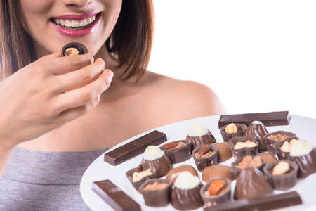 taste: Cheerful young woman holding plate with delicious chocolate candies over white background. Close-up. Stock Photo