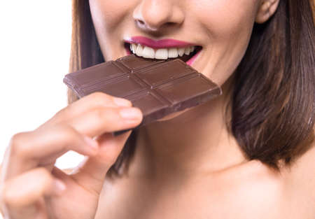 Young beautiful shirtless woman eating bar of  dark chocolate. Studio shot. Close-up.