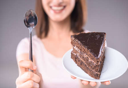 one people: Sweet temptation. Young woman holding plate with chocolate cake and dessert spoon. Stock Photo