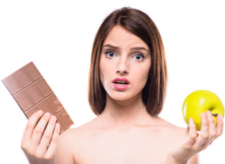 difficult decision: Difficult decision. Worried shirtless woman choosing between chocolate and  apple. Healthy lifestyle concept.