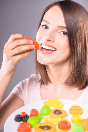 sweettooth: Sweet-tooth. Beautiful happy woman holding plate with  fruit jellies over gray background.