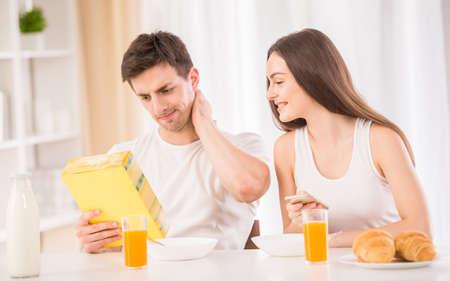 comiendo cereal: Desayuno en la cocina. Hombre atractivo joven que intenta preparar copos de maíz, mientras que su novia que usa su teléfono y sonriente.