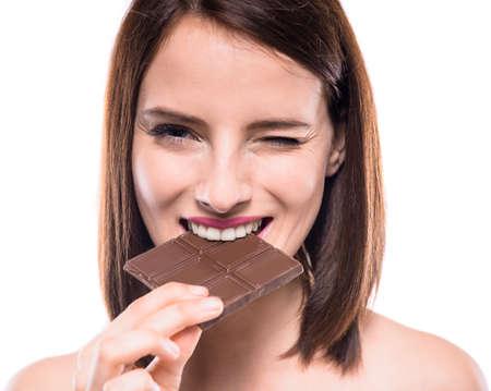 yummy: Flirty beautiful woman eating bar of chocolate and looking at camera. Studio shot. Stock Photo