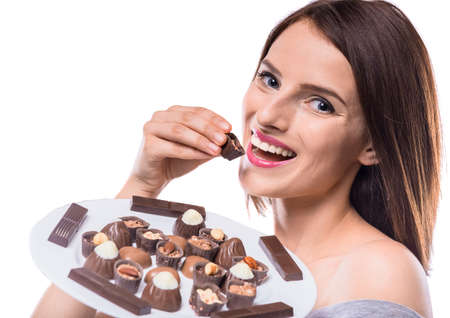 sweettooth: Happy sweet-tooth. Beautiful woman holding plate with various of chocolates.