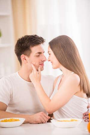 petit dejeuner romantique: Jeune couple ayant le petit d�jeuner romantique � la maison dans la cuisine.