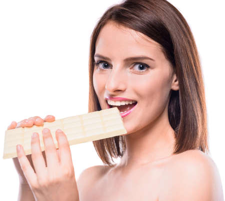 flirty: Flirty beauty. Shirtless woman tasting bar of  white chocolate over white background. Studio shot. Stock Photo