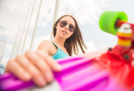 cheeful: Portrait of cheeful woman in sunglasses holding skateboard in her hands.