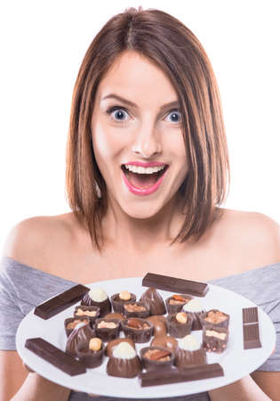 sweettooth: Amazed sweet-tooth. Beautiful woman holding plate with various of chocolates.
