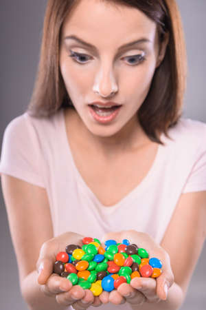 sweettooth: Amazed sweet-tooth. Beautiful woman holding colorful chocolate drops, gray background. Stock Photo