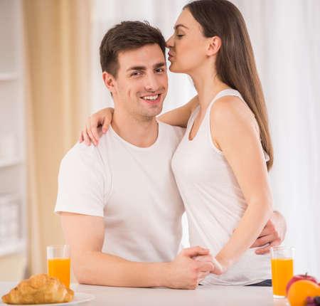 desayuno romantico: Pareja joven con desayuno romántico en casa en la cocina.