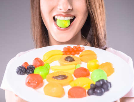 sweettooth: Sweet-tooth. Young woman holding plate with  fruit jellies over gray background. Close-up.