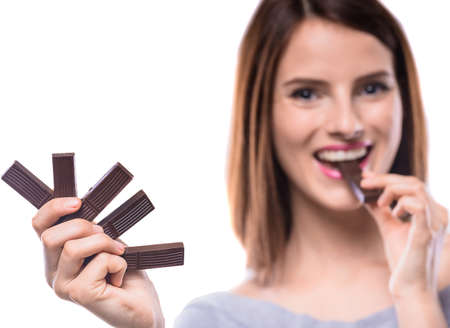 sweettooth: Sweet-tooth. Cheerful young woman tasting delicious chocolate candies, white background. Focus on hand.