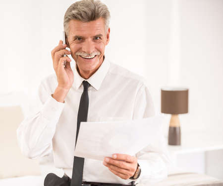telephoning: Cheerful businessman talking by phone and holding his papers while sitting on bed at the hotel room.