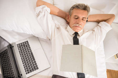 tired eyes: Top view of business man is sleeping in suit with notebook and laptop on bed at the hotel room. Stock Photo