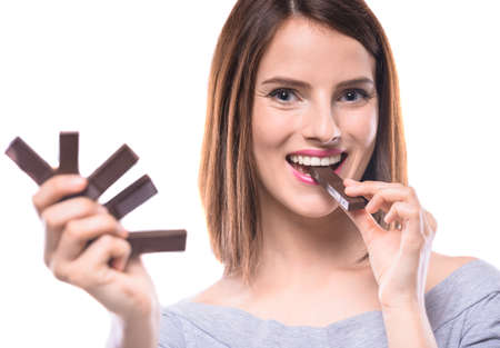 sweettooth: Sweet-tooth. Cheerful young woman tasting delicious chocolate candies, white background.