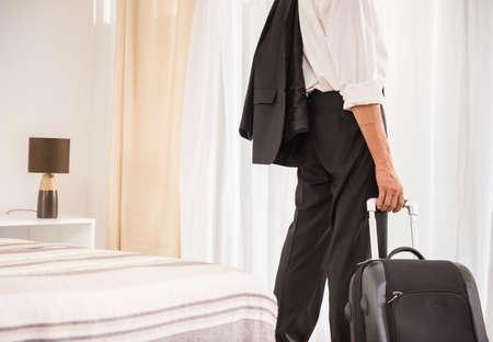 ホテルの部屋で彼のスーツケースを持ったビジネスマン。背面図。クローズ アップ。