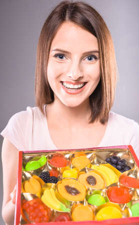 sweettooth: Sweet-tooth. Beautiful woman holding box of  fruit jellies over gray background. Stock Photo