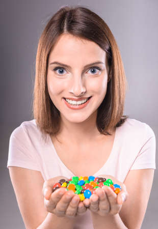 sweettooth: Happy sweet-tooth. Beautiful woman holding colorful chocolate drops, gray background.