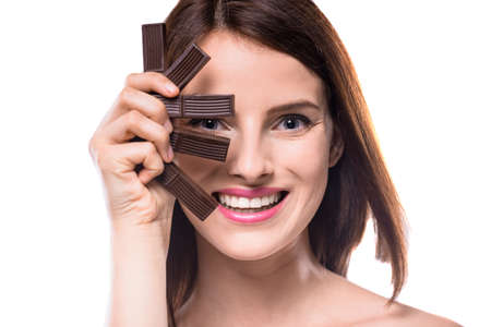 sweettooth: Sweet-tooth. Cheerful young woman holding delicious chocolate candies, white background.