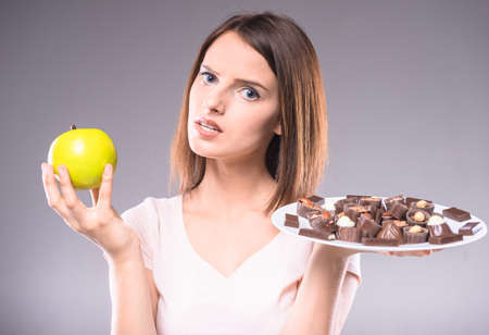 difficult decision: Difficult decision. Worried woman choosing between chocolates and  apple. Healthy lifestyle concept.