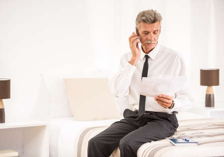 telephoning: Businessman talking by phone and holding his papers while sitting on bed at the hotel room. Stock Photo