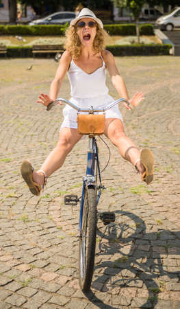 Attractive woman riding on bicycle in the city street and having fun.