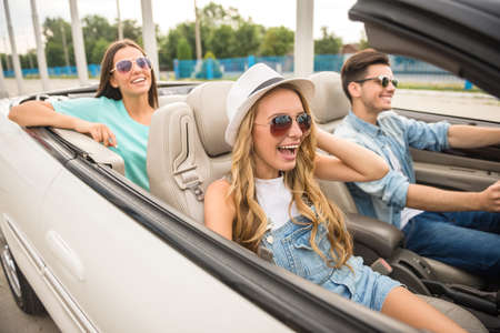 cabriolet: Three happy friends in sunglasses traveling in the cabriolet. Stock Photo