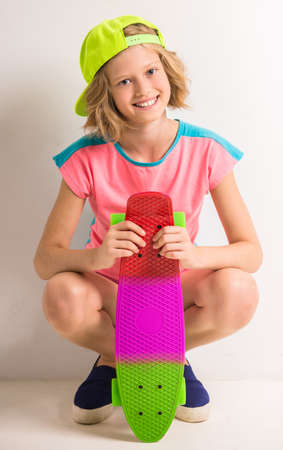 peaked: Cute girl in peaked cap holding colored skateboard against white background.