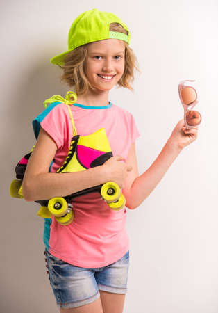 peaked: Smiling girl in peaked cap with roller skates on her shoulder holding sunglasses against white background. Stock Photo