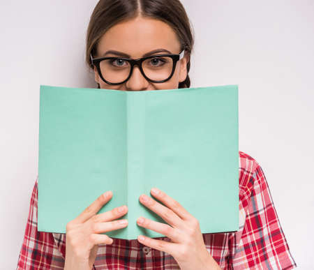 school girl sexy: Smiling clever girl in glasses covering the mouth with book on white background.