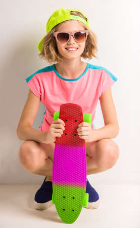 peaked: Cute girl in peaked cap and sunglasses holding colored skateboard against white background.