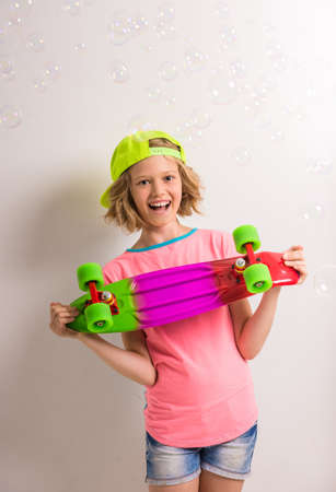 peaked: Young girl in peaked cap with skateboard having fun against white background. Stock Photo
