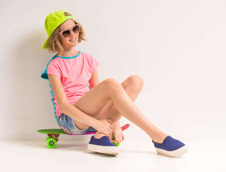 peaked: Beautiful girl in peaked cap and sunglasses sitting on skateboard and looking away against white background.