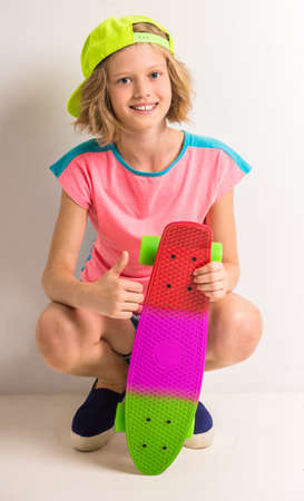 peaked: Young girl in peaked cap with skateboard showing thumb up against white background.