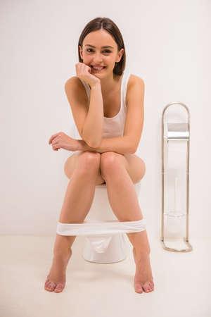 diarrea: El uso del inodoro. Una joven mujer utiliza un inodoro con un rollo de papel higiénico en la mano.