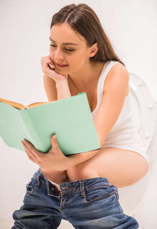 Young woman reading a book while sitting in the toilet Stock Photo