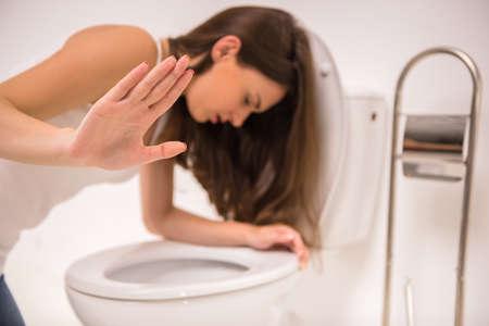 borracho: Mujer joven vomitando en la taza del inodoro en las primeras etapas del embarazo o después de una noche de fiesta y beber.