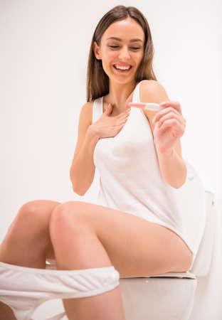 prueba de embarazo: Mujer que sostiene la prueba de embarazo con dos rayas. Muchacha preocupante mirando la prueba de embarazo en el baño