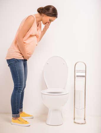 persona enferma: Joven embarazada usar el inodoro, aislado en un fondo blanco