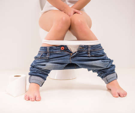 sit: Using toilet. A young woman uses a toilet with a roll of toilet paper in his hand. Stock Photo