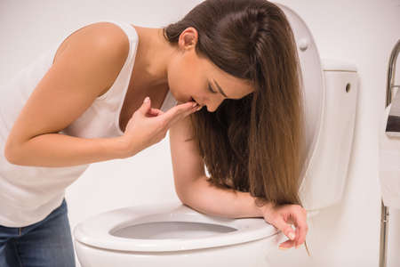Young woman vomiting into the toilet bowl in the early stages of pregnancy or after a night of partying and drinking. Stock Photo