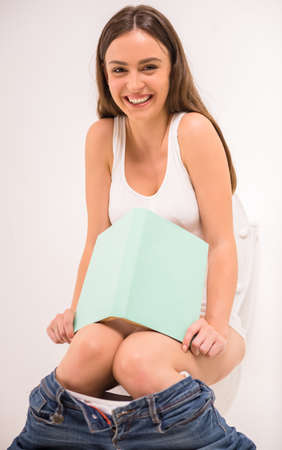 toilet roll: Young woman reading a book while sitting in the toilet Stock Photo