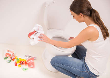 early pregnancy: Young woman vomiting into the toilet bowl in the early stages of pregnancy or after a night of partying and drinking. Stock Photo