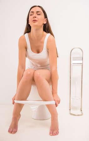 pis: El uso del inodoro. Una joven mujer utiliza un inodoro con un rollo de papel higiénico en la mano.