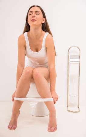 pee pee: Using toilet. A young woman uses a toilet with a roll of toilet paper in his hand. Stock Photo