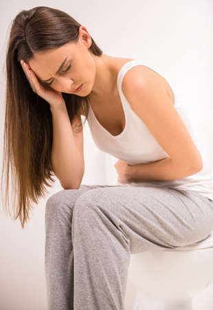 constipation: Using toilet. A young woman uses a toilet with a roll of toilet paper in his hand. Stock Photo