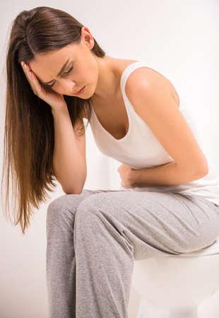 Verwendung WC. Eine junge Frau verwendet eine Toilette mit einer Rolle Toilettenpapier in der Hand.