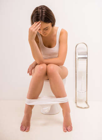 hemorrhoids: Using toilet. A young woman uses a toilet with a roll of toilet paper in his hand. Stock Photo